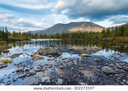 Rischorr mountain reflection in shallow Polygonal northern taiga forest lake with small rocks on foreground, Hibiny mountains above the Arctic Circle, Russia - stock photo