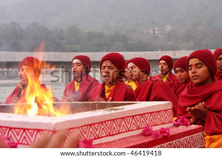 RISHIKESH, INDIA - JANUARY 19: Hindu students from the Parmath Niketan Ashram hold ceremonial lanterns during the daily aarti prayer on the River Ganges, January 19, 2009 in Rishikesh, India. - stock photo