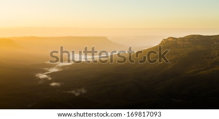 Rising sun illuminates clouds and mist in the valley from Sublime Point overlooking the majestic Blue Mountains near Sydney NSW Australia - stock photo