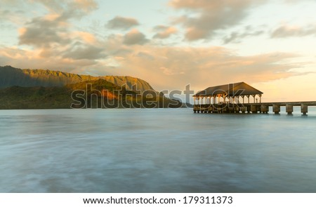 Rising sun illuminates the peaks of Na Pali mountains over the calm bay and Hanalei Pier in long exposure photo - stock photo