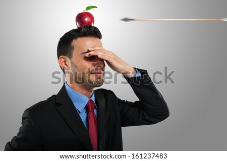 Risk management concept, arrow hitting an apple on a businessman's head - stock photo