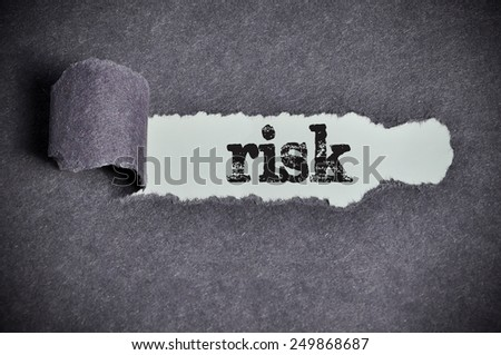 risk word under torn black sugar paper  - stock photo