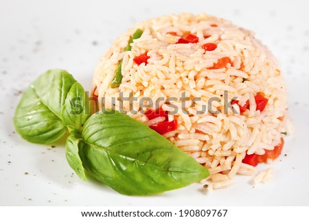 Risotto of spring vegetables with basil twig - stock photo