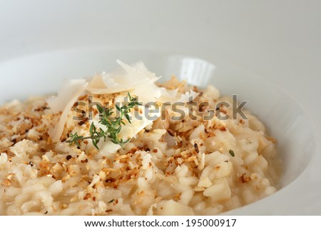 Risotto topped with shaved Parmesan and thyme - stock photo