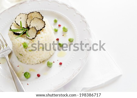 Risotto with green peas, black truffle and red pepper on white plate and table - stock photo