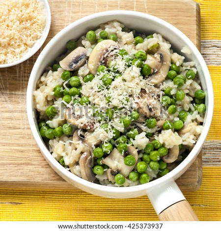 Risotto with mushrooms, peas and parmesan.  Overhead view. - stock photo