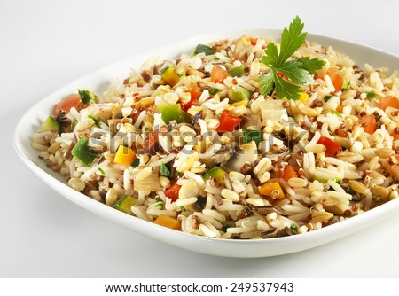 Risotto with quinoa and vegetables on white plate - stock photo