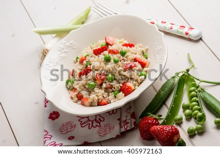 risotto with strawberries and green peas - stock photo