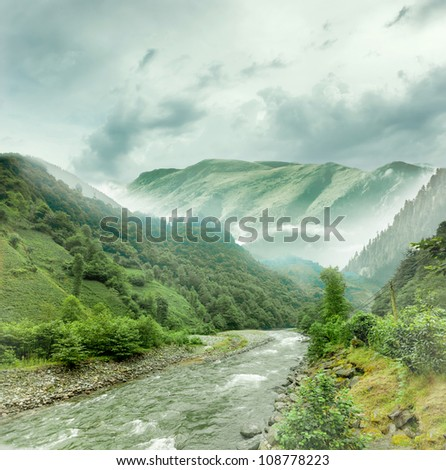 River coming from foggy mountains - stock photo