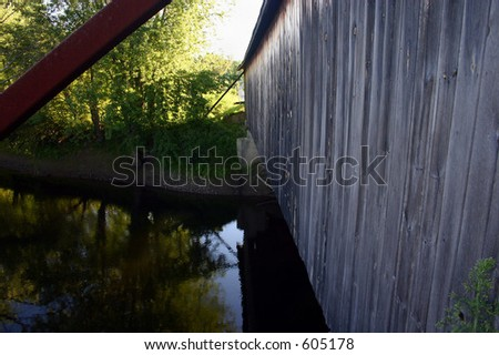 River flowing under covered bridge - stock photo
