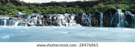 River Hvita sends glacial water flowing through layers of lava field at Hraunfossar waterfall Iceland Europe - stock photo