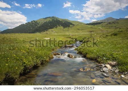 River in mountain valley with bright meadow. Natural summer landscape in baqueira beret, north of catalonia, spain, europe - stock photo