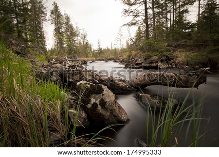 River in wilderness photographed with long exposure  - stock photo