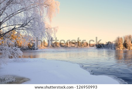 River in winter and tree branches covered with white frost - stock photo