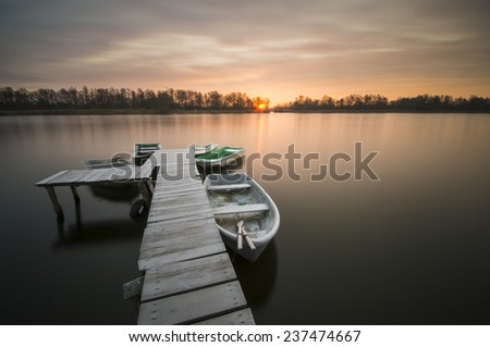 river in winter,fishing boats moored at the  small wooden bridge over the river - stock photo