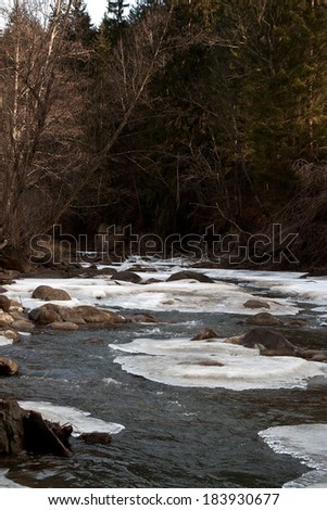 River in winter. Ice on river in frosty winter sunset  - stock photo