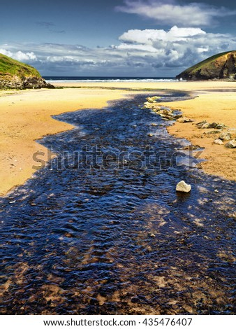 River meets the sea; small river flows across sand and into the ocean  - stock photo