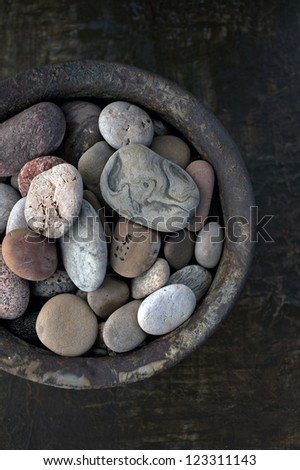 River stones collected in a rust bowl. - stock photo