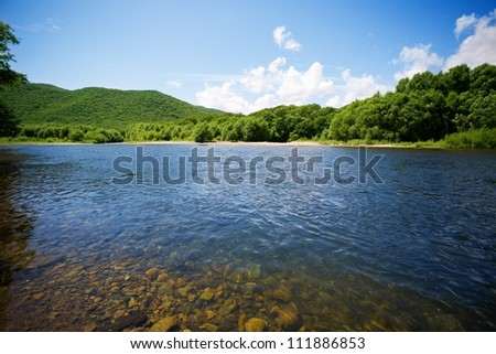 River summer landscape with bright blue sky and clouds. - stock photo