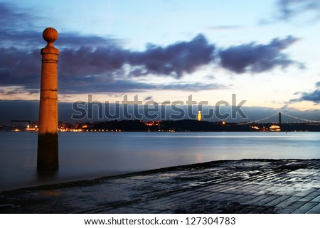 River view from the beach at sunset. City lights on other margin and bridge - stock photo