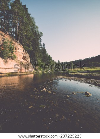 river with reflections in weater and sandstone cliffs in latvia - retro, vintage style look - stock photo