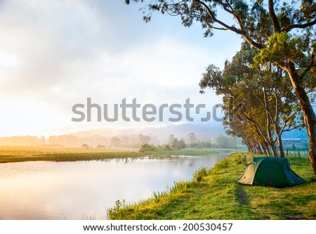 Riverside campsite in a morning light - stock photo