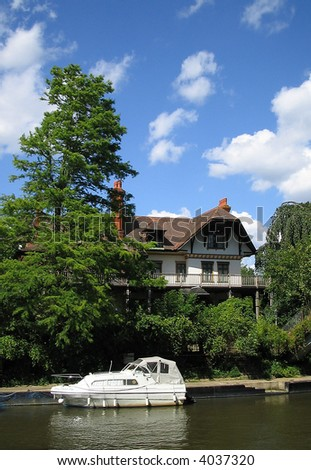 Riverside house with moored boat. - stock photo