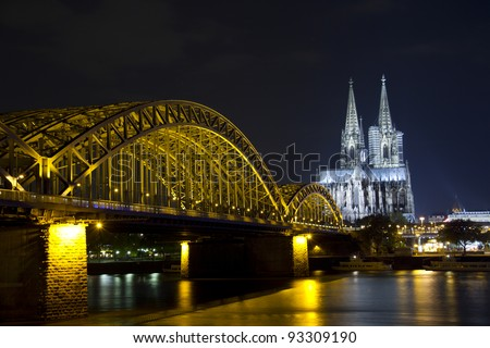 Riverside view of the Cologne Cathedral and railway bridge over the Rhine river in Germany at night - stock photo