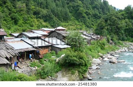 Riverside village at the base of the Himalayas, India - stock photo