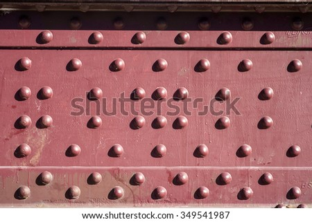 rivets in a red steel plate - stock photo