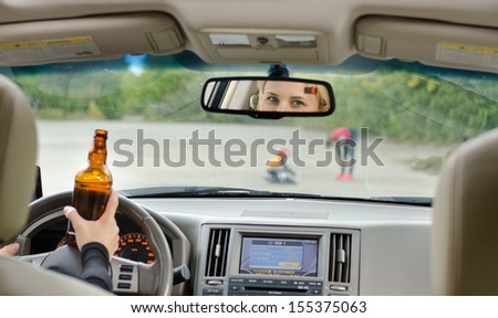 Road accident due to alcohol about to happen as a drunk female driver clutching her bottle of booze in one hand while driving approaches young children playing in the road - stock photo