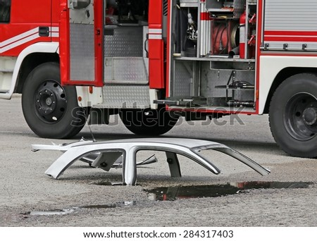 road accident with white car parts and the firetruck - stock photo