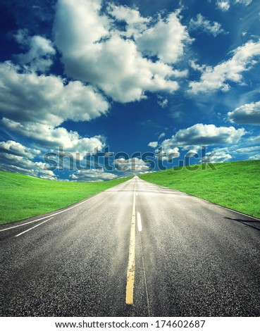 Road across the meadow with roadsign - stock photo