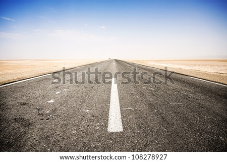 Road across the salt lake of Chott El Djerid, Tunisia. - stock photo
