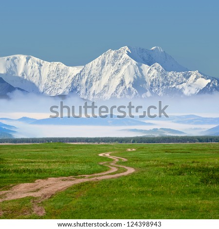road among a fields to a mountains - stock photo