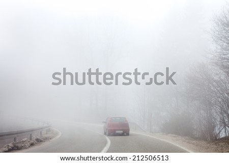 Road and a car in fog - stock photo