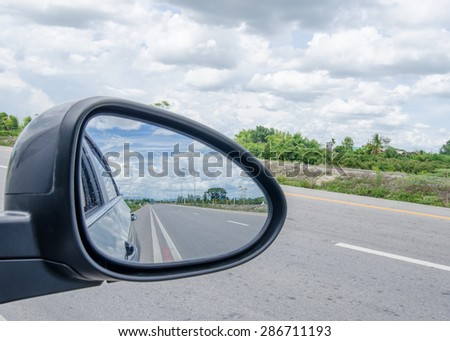 road and blue sky,rear view in car mirror - stock photo