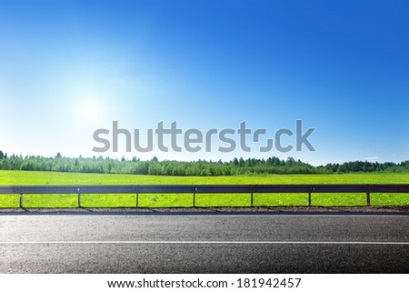 road and field of spring grass - stock photo