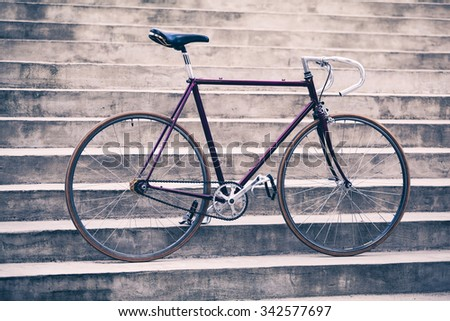 Road bicycle, fixed gear bike on city concrete street. Urban industrial cycling, bike on city stairs steps bicycle closeup, vintage old retro bike, cycling or ecology commuting. Industrial concept. - stock photo