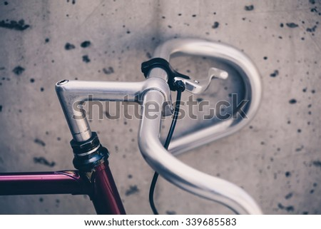 Road bicycle handlebar details, fixed gear bike on city concrete street. Urban industrial cycling, city scene bike closeup details, vintage old retro bike, ecology commuting. Industrial concept. - stock photo
