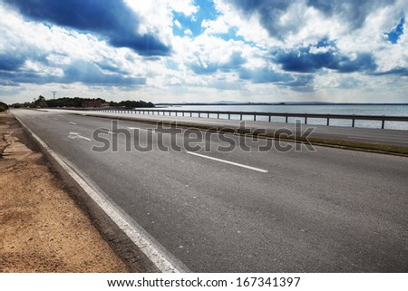road by the sea on a sunny day - stock photo
