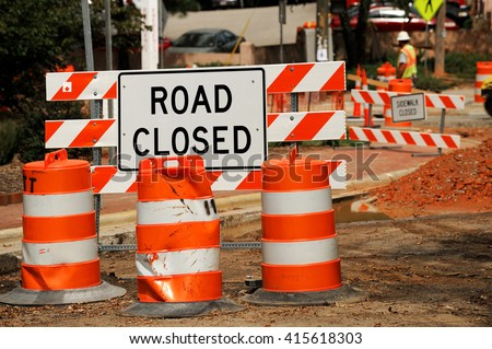 road closed sign and traffic cone in the street - stock photo