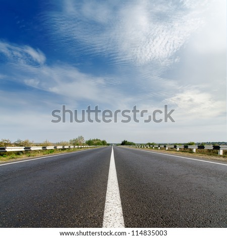 road closeup under cloudy blue sky - stock photo