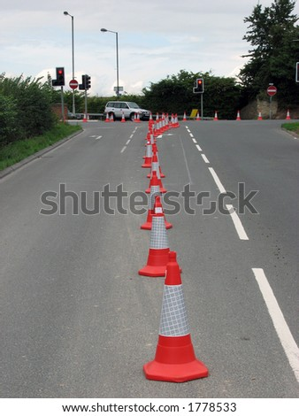 Road cones channeling traffic at road junction - stock photo
