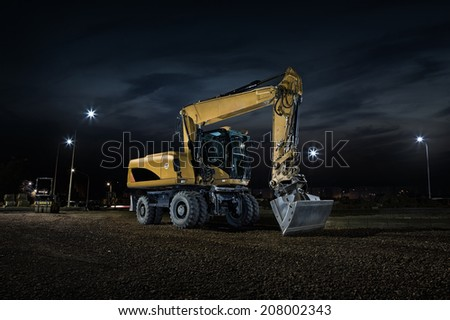 Road construction, close up of excavator at night - stock photo