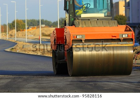 Road construction. Large rolling machinery paving a road - stock photo