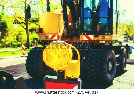 Road construction site in city with excavator and yellow flash signal. Toned. - stock photo