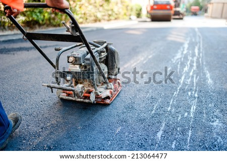 road construction with worker paving the fresh bitumen or asphalt - stock photo