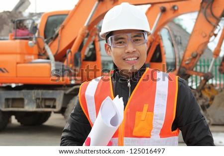 road construction worker standing front of excavator shot ...