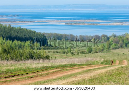 Road COUNTRY in spring day. Country road to the forest in spring day. Country road between green field at summer and blue clean sky. Nature conceptual image. - stock photo